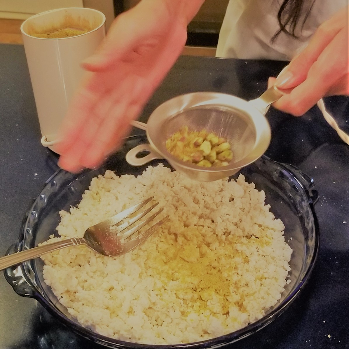 G. sifting in pistachi powder